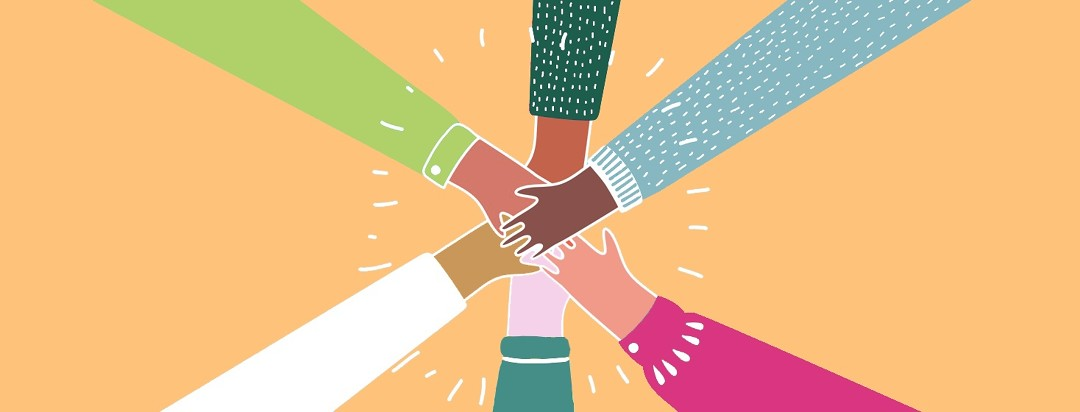 Six hands all placed together by people standing in a circle.