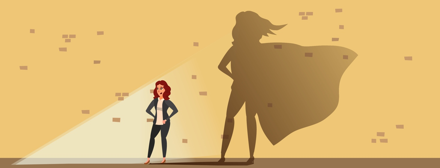 Woman, standing in front of a spotlight. Behind her, her reflection appears against a wall, and in the reflection, she is wearing a superhero