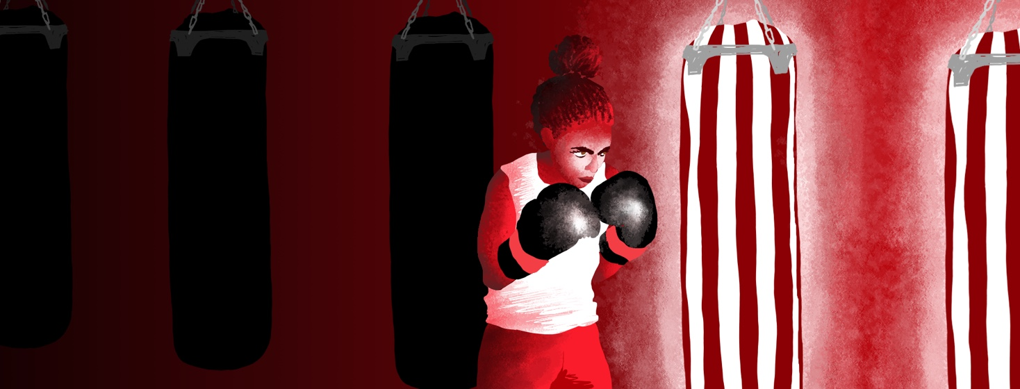 A boxer stands in front of several punching bags that are dark and receding into the background, and behind a punching bag that is lit up and in full color, ready for her to take on this next obstacle.