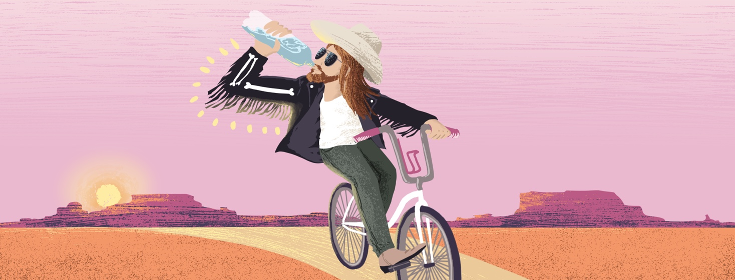 A man strongly resembling Billy Ray Cyrus confidently rides a bike while also drinking water.