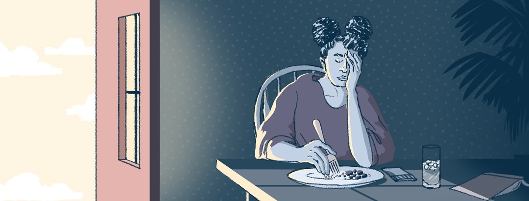 An exhausted woman in a dark room (which is in contrast to the bright world outside her window) pauses in eating her meal to rest her head in her hand.