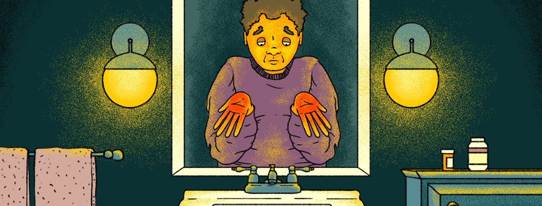 A sad, tired-looking man with jaundice stands in front of a bathroom mirror with his palms (which are red) facing outward.