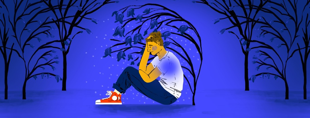 A depressed man sitting on the ground with his hand in his hair sits under a drooping blue tree against a blue background.