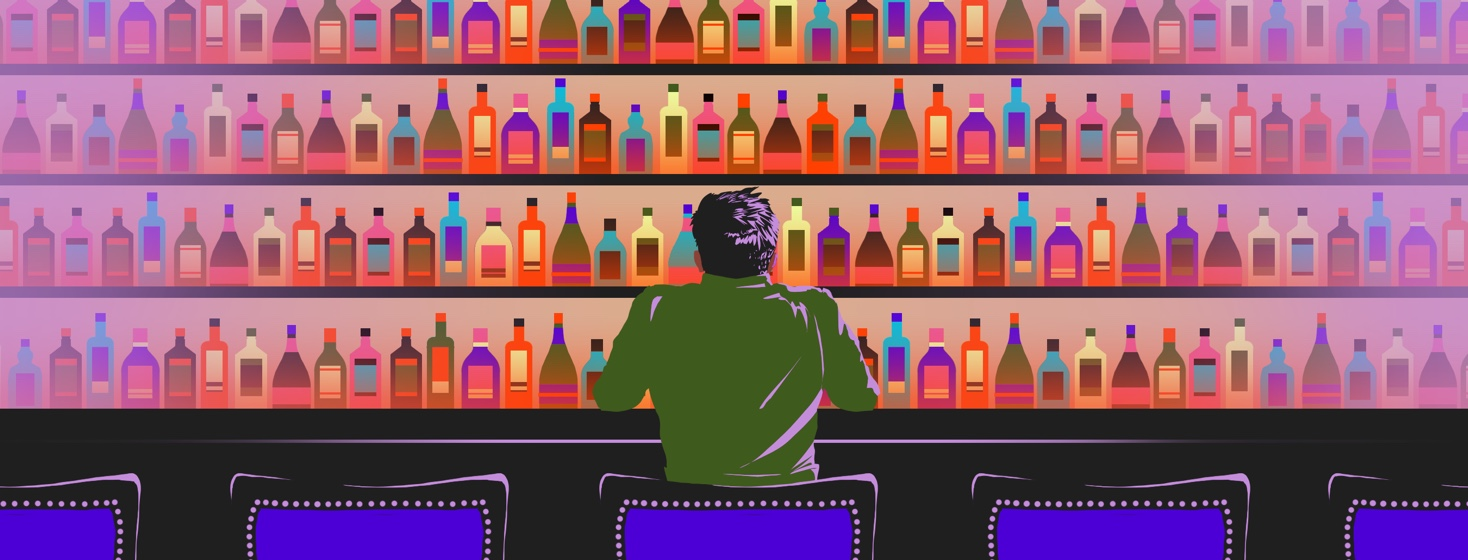 A man sits at a bar, staring at the shelves of alcohol in front of him.