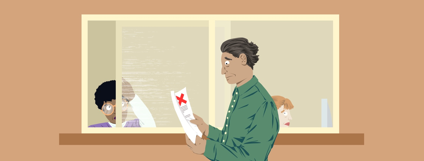 A man looks dejected while looking at a piece of paper with a big red 'X' on it. He is standing next to the reception window at a doctor's office. A receptionist is closing the window and looking at the man with pity.