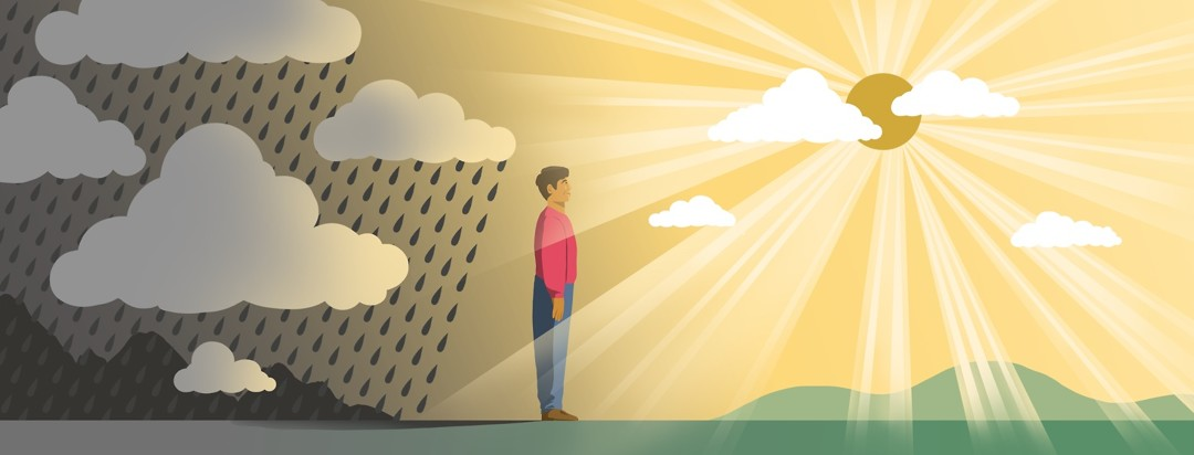 A man stands between rain clouds (behind him) and a sun emerging from white clouds.