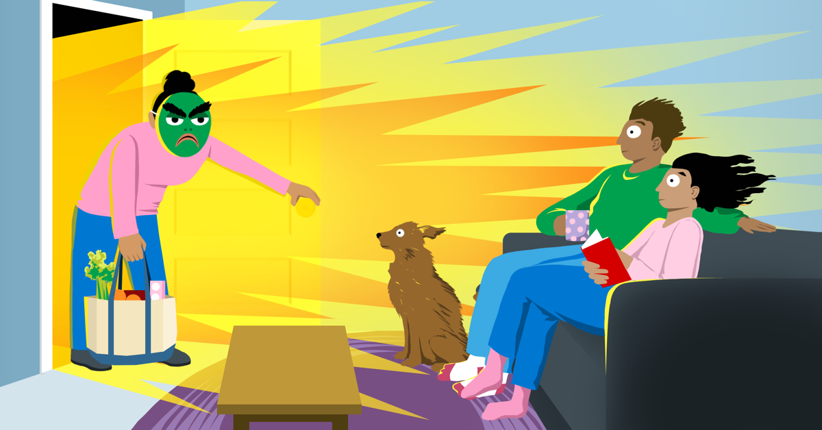 A woman wearing a very grumpy mask bursts through a door, blowing the hair back on a couple sitting on the couch and a dog on the floor.