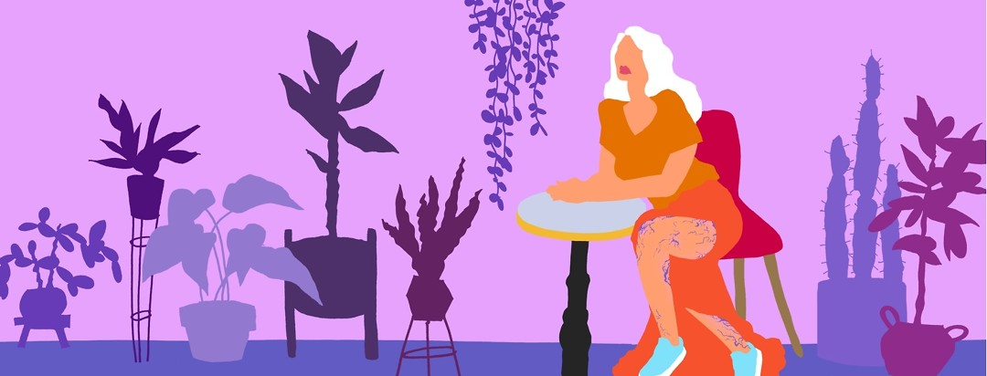 A woman seated at a table surrounded by house plants is wearing a long dress that partially reveals her legs which are covered in purple veins.