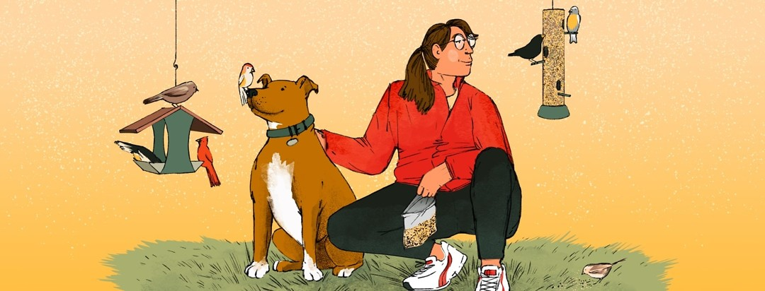 A woman crouches down with her hand on a dog next to her. The woman is smiling and looking off at a bird feeder filled with birds. The dog has a bird perched on his nose and is sitting next to another feeder.