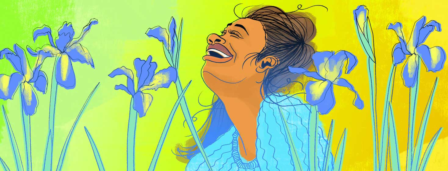 a woman is in a field of iris flowers blooming, looking up with a joyous and hopeful expression.