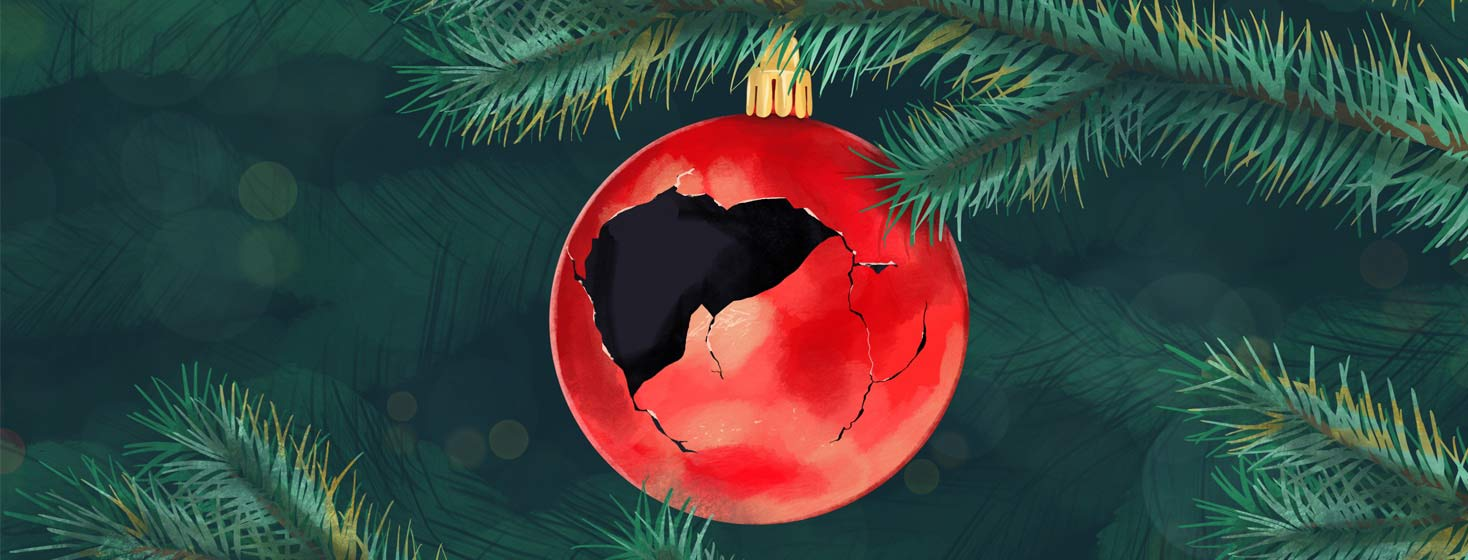 a shattered glass Christmas tree ornament has a liver-shaped hole created from the broken bits