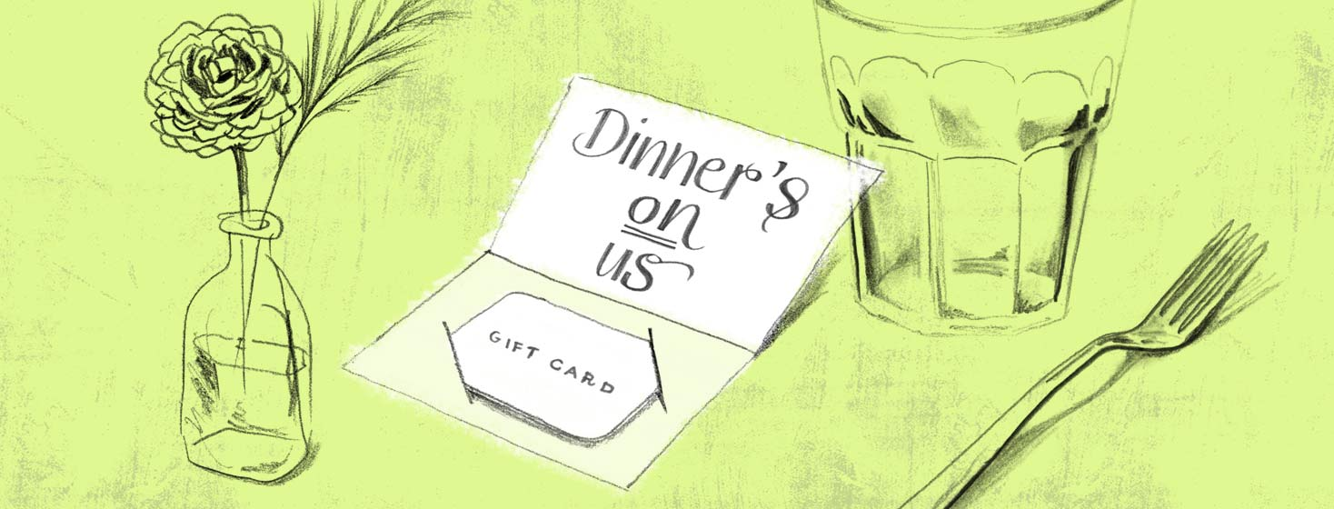 a gift card is laid on the table with a small vase of flowers, a fork, and drinking glass.